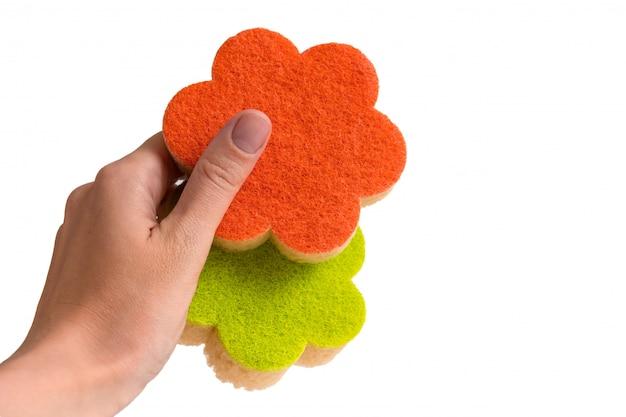 Spugne per lavare i piatti in una mano femminile su un bianco isolato Foto Premium