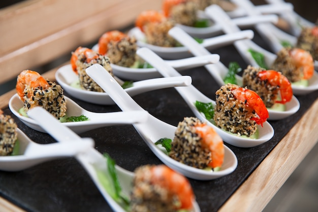 Spuntini con gamberetti in cucchiai sul tavolo del buffet Foto Gratuite