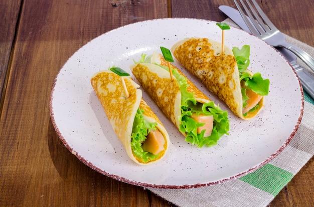 Spuntini da pancake, salmone e foglie di insalata verde. Foto Premium