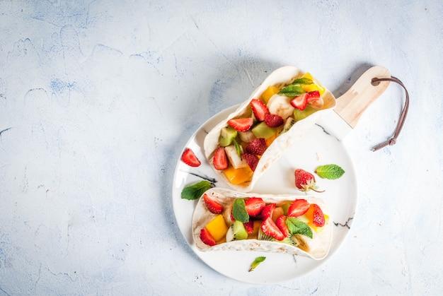 Spuntini estivi. cibo per una festa. tacos alla frutta con fragole, mango, banane, cioccolato, menta. su un tavolo di cemento azzurro. vista dall'alto di copyspace Foto Premium