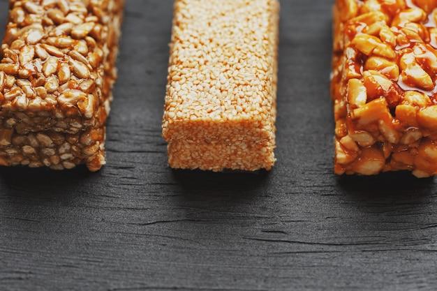 Spuntini sani. cibo dieta fitness. barretta di cereali con arachidi, sesamo e semi su un tagliere su un tavolo scuro, barrette energetiche Foto Premium