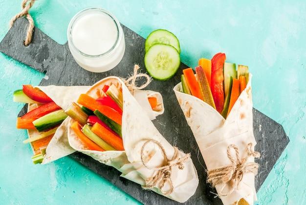 Spuntino salutare estivo panino alla tortiglia in stile messicano avvolge assortiti bastoncini di verdure fresche colorate (sedano pepe rabarbaro cetriolo e carota) con salsa allo yogurt tuffo sfondo azzurro Foto Premium