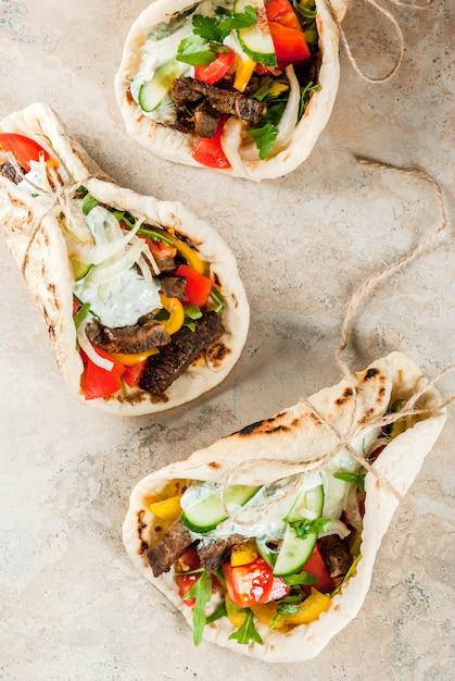 Spuntino salutare, pranzo. gyros sandwich tradizionali greci avvolti - tortillas, pita di pane con ripieno di verdure, carne di manzo e salsa tzatziki Foto Premium