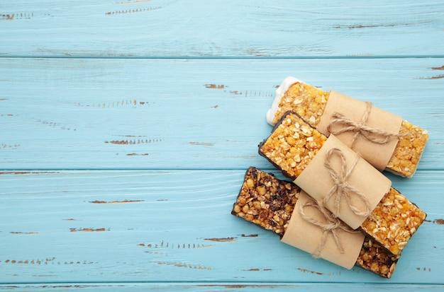 Spuntino sano, barrette di muesli con uvetta e bacche secche su una parete blu Foto Premium