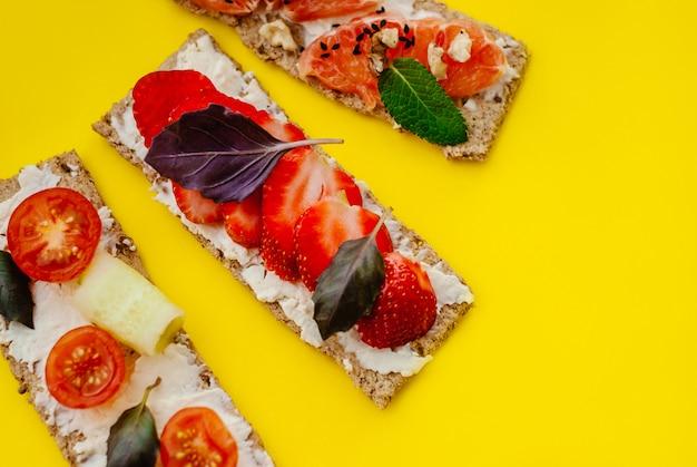 Spuntino sano con pane croccante, crema di formaggio, fragola, pompelmo, pomodoro e cetriolo su uno sfondo giallo Foto Premium