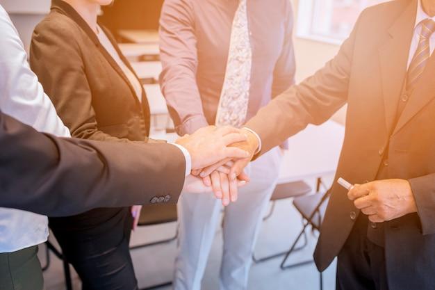 Squadra corporativa che impila la mano a vicenda nell'ufficio Foto Gratuite