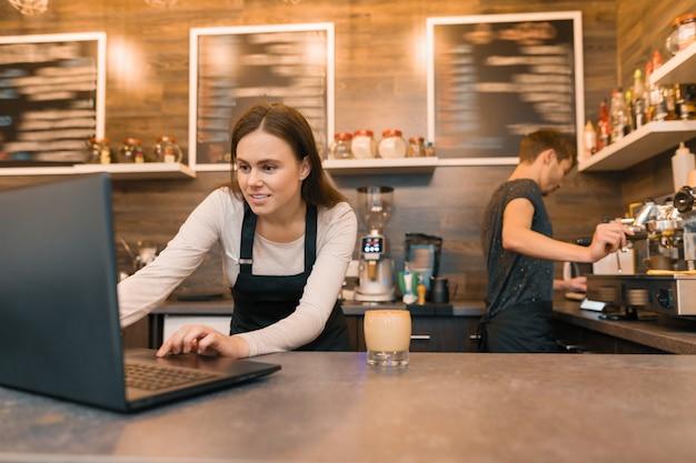 Squadra degli operai della caffetteria che lavorano vicino al contatore con il computer portatile e che producono caffè, Foto Premium