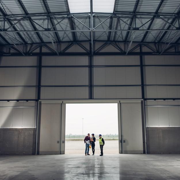 Squadra dell'architetto sul luogo di lavoro con le cianografie Foto Premium