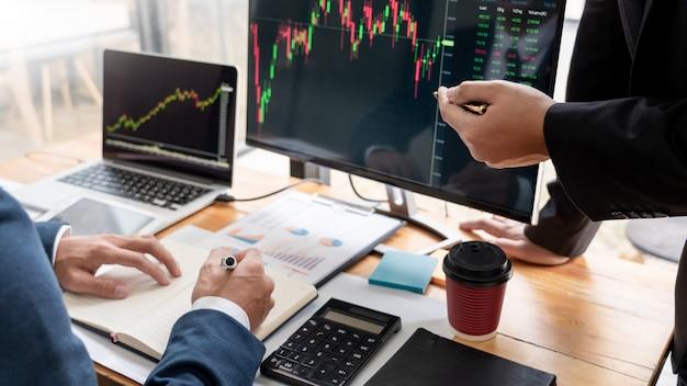 Squadra di agenti di borsa che discutono con schermi di visualizzazione analizzando dati, grafici e rapporti di trading di borsa per gli investimenti Foto Premium