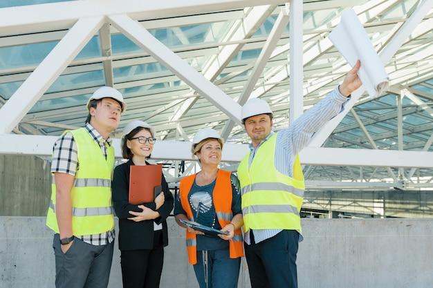 Squadra di costruttori ingegnere architetto sul tetto del cantiere. Foto Premium