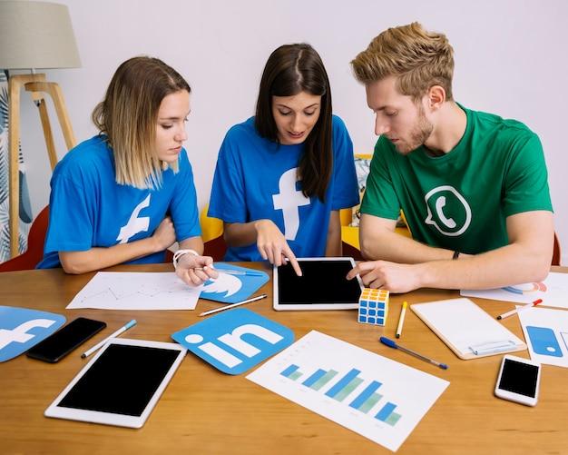 Squadra di social media networking guardando la tavoletta digitale in ufficio Foto Gratuite