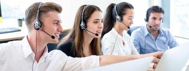 Squadra di telemarketing che lavora insieme in ufficio call center Foto Premium