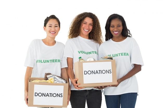 Squadra di volontari che sorridono alle caselle di donazioni della holding della macchina fotografica Foto Premium