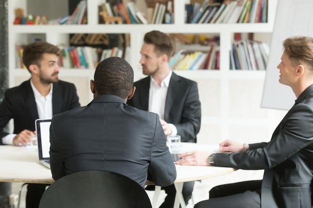 Squadra multietnica di colleghi maschi che discutono di piani aziendali durante il briefing. Foto Gratuite