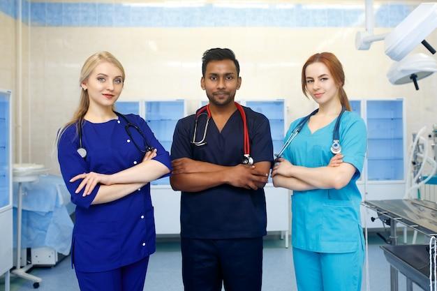 Squadra multirazziale di giovani medici in un ospedale in piedi in una sala operatoria Foto Premium
