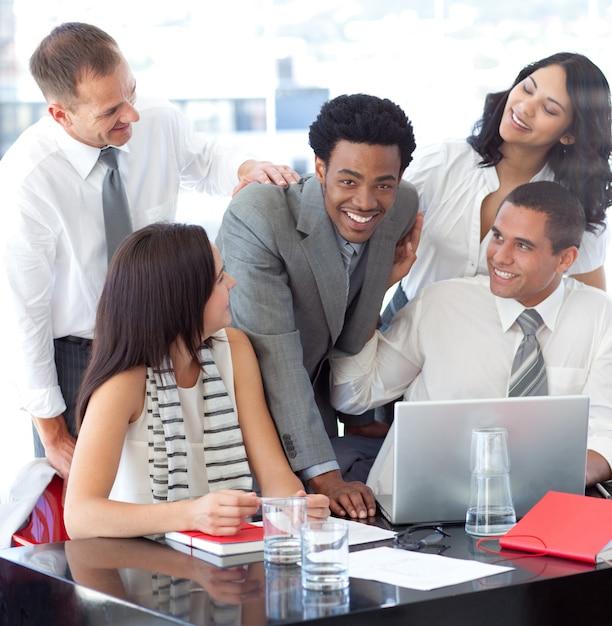 Squadra sorridente di affari che lavora con un computer portatile Foto Premium