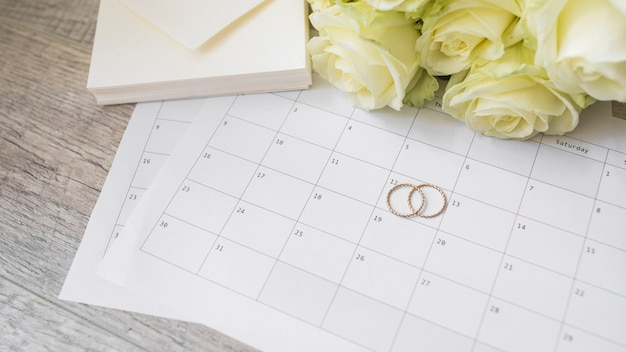 Stack di buste; rose e fedi nuziali sul calendario sul tavolo di legno Foto Gratuite