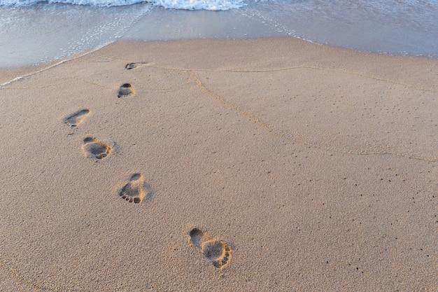 Stampa del piede nella sabbia sullo sfondo spiaggia Foto Premium