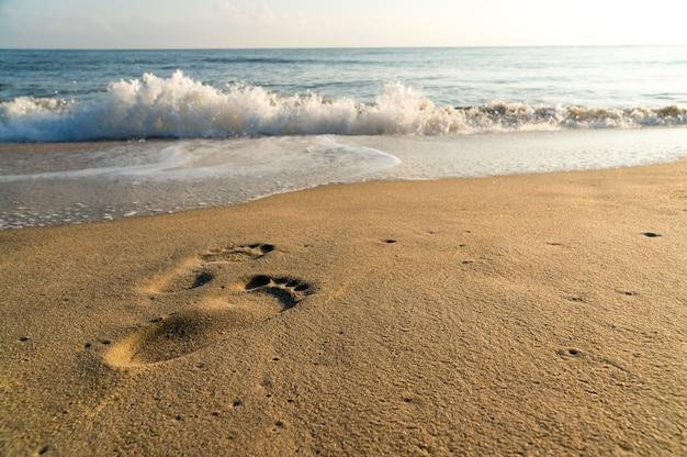 Stampa del piede umano sulla spiaggia con piccole onde e cielo blu Foto Premium