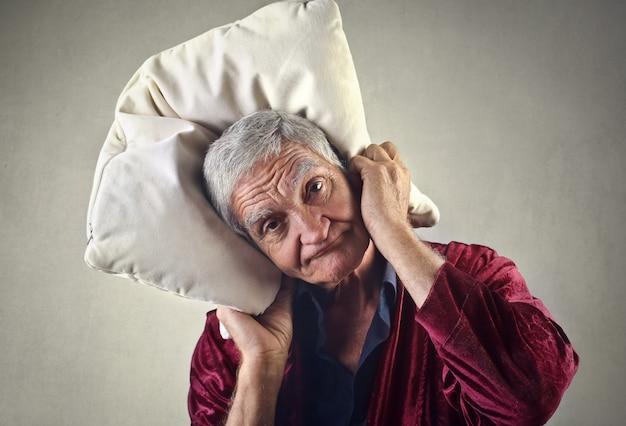 Stanco vecchio con un cuscino Foto Premium