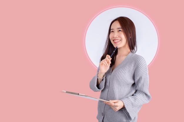Stare di pensiero della bella donna dell'asia isolato su fondo rosa Foto Premium