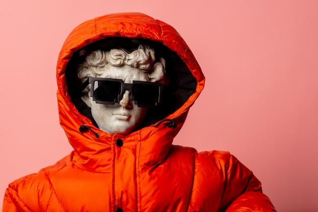 Statua antica vestita di piumino e occhiali da sole Foto Premium