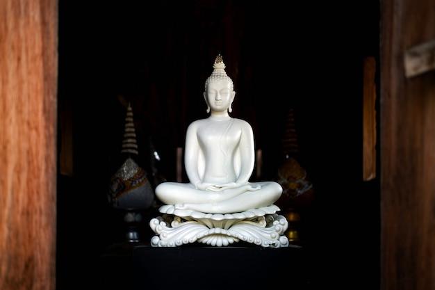 Statua bianca del buddha in tempiale tailandese di lanna Foto Premium