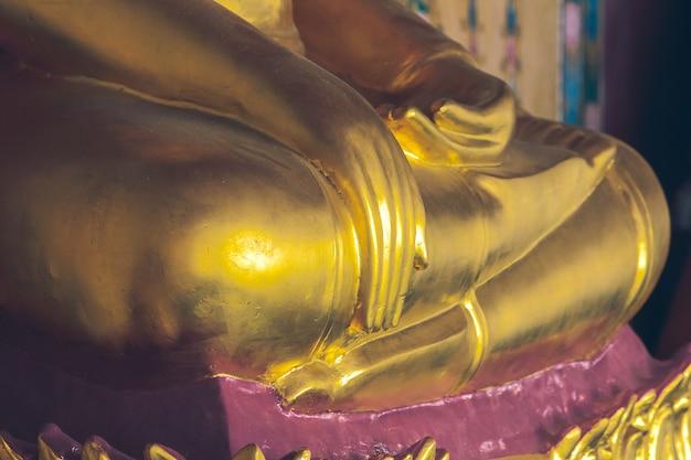 Statua dorata del buddha sul piedistallo con vecchie pareti Foto Premium