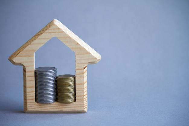 Statuetta in legno di casa e due colonne di monete all'interno su grigio Foto Premium