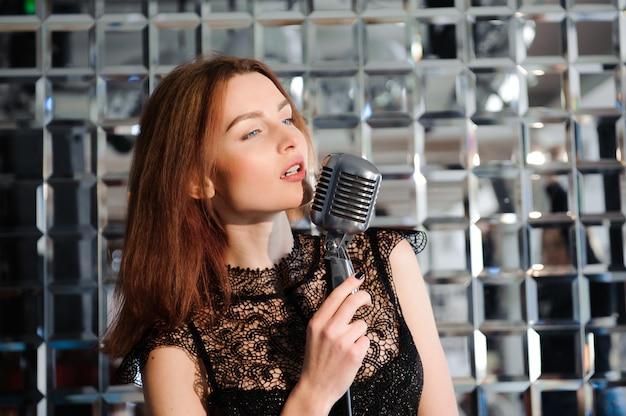 Stella del rock. ragazza sexy che canta nel microfono retrò. Foto Premium