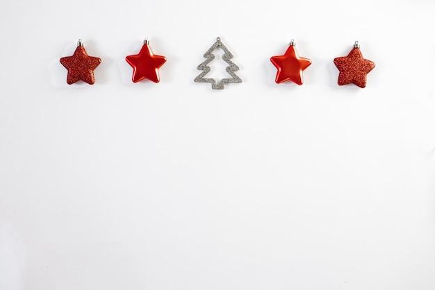 Stelle di natale rosso-bordo di natale giocattoli dell'albero di natale ed albero di natale su fondo bianco, insegna orizzontale. biglietto di auguri per natale o capodanno. copyspace Foto Premium