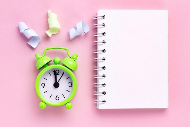 Stelle filanti colorate e una sveglia su uno sfondo rosa Foto Premium