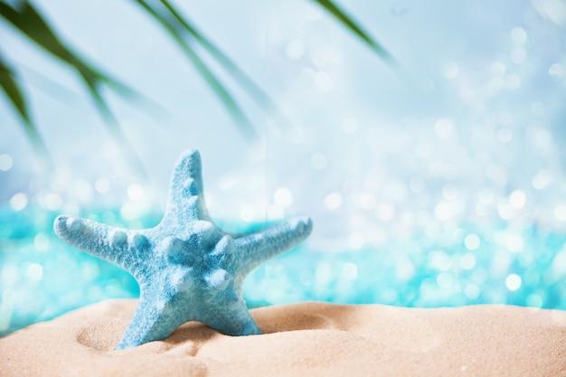 Stelle marine rosse in una sabbia bianca sotto una foglia di palma Foto Premium