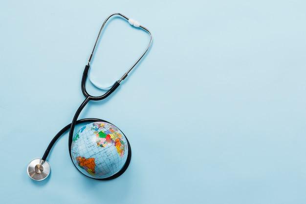 Stetoscopio che abbraccia la terra su sfondo blu Foto Gratuite