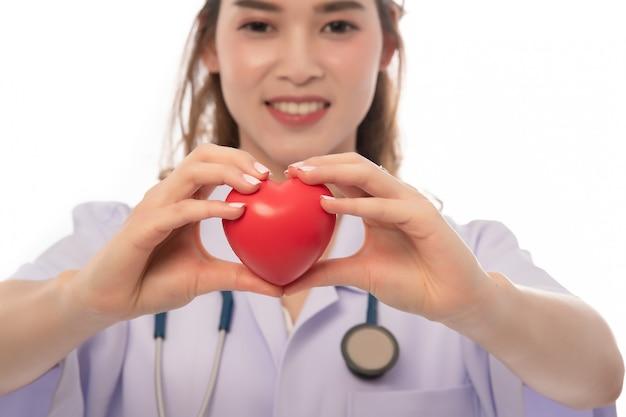 Stetoscopio con cuore in mani del medico isolate sul primo piano bianco, copyspace, sanità. Foto Premium