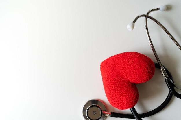 Stetoscopio con cuore rosso su sfondo bianco. concetto di assistenza sanitaria e medicina Foto Premium