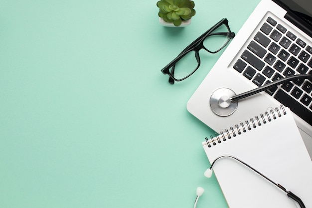 Stetoscopio; diario a spirale; spettacolo e pianta succulenta con laptop su sfondo verde Foto Gratuite