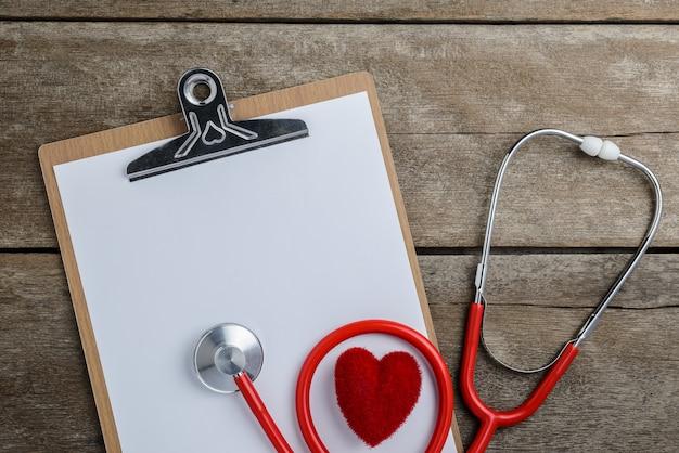 Stetoscopio medico con appunti e cuore sul tavolo di legno Foto Premium