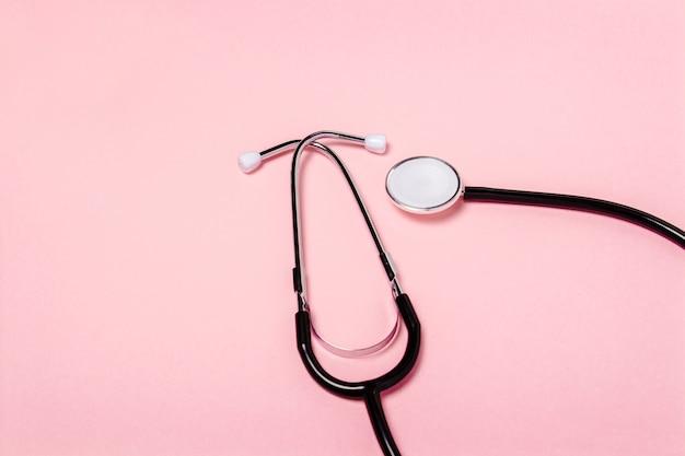 Stetoscopio medico su una superficie rosa. concetto di assistenza sanitaria, medicina, virus, epidemia, alta qualità, il migliore al mondo. . vista piana, vista dall'alto Foto Premium