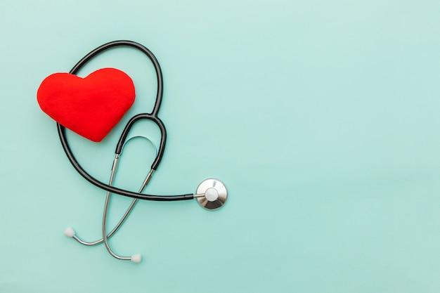 Stetoscopio o phonendoscope dell'attrezzatura della medicina e cuore rosso isolati su fondo blu pastello d'avanguardia. Foto Premium