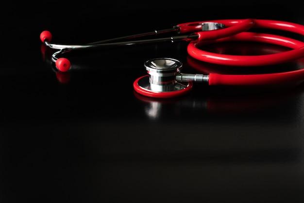 Stetoscopio rosso su sfondo nero. concetto di assistenza sanitaria e medicina Foto Premium