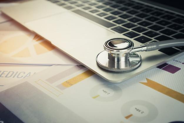 Stetoscopio sul calcolatore con i risultati della prova nel fondo della stanza di consulto di medico e nel grafico di rapporto per medico Foto Premium