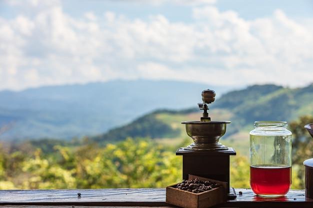 Stile classico della smerigliatrice di caffè antica sullo scaffale e sulla montagna con la natura del cielo della nuvola Foto Premium