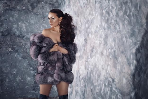 Stile di moda invernale. bella donna in pelliccia di lusso sul corpo nudo con stivali sopra il ginocchio. Foto Premium
