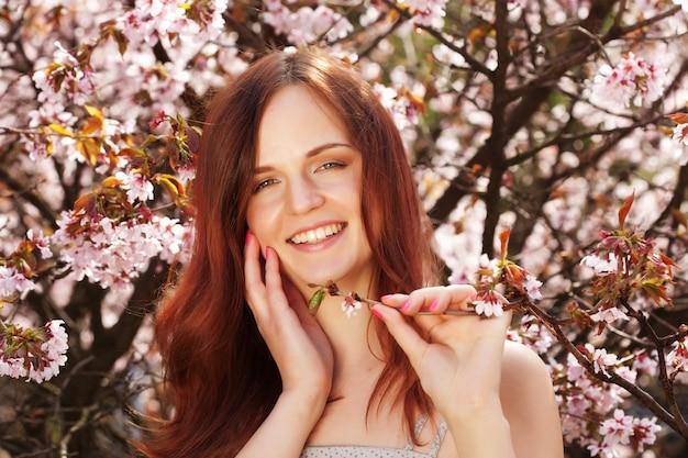 Stile di vita e persone bella donna in giardino fiorito Foto Premium