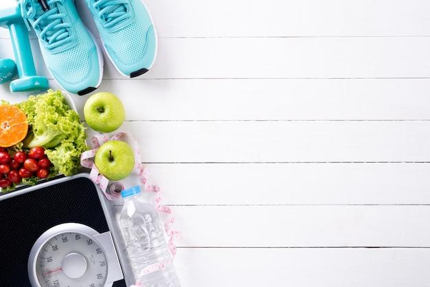 Stile di vita sano, cibo e concetto di sport su legno bianco Foto Premium
