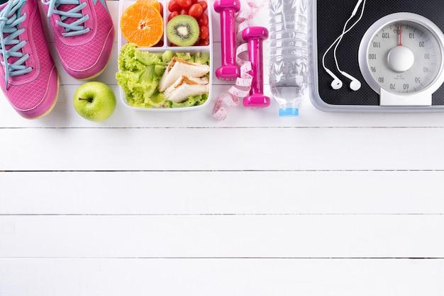 Stile di vita sano, cibo e sport su fondo di legno bianco. Foto Premium