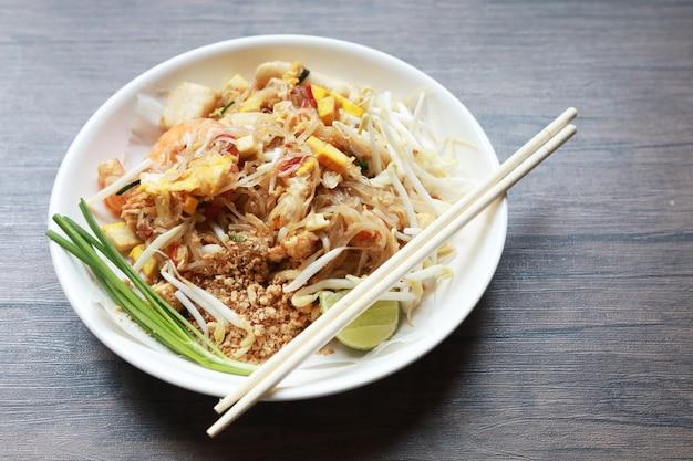 Stile tailandese della tagliatella fritta con il gamberetto tailandese, stile tailandese della tagliatella della tailandia dei gamberetti sulla tavola di legno. Foto Premium
