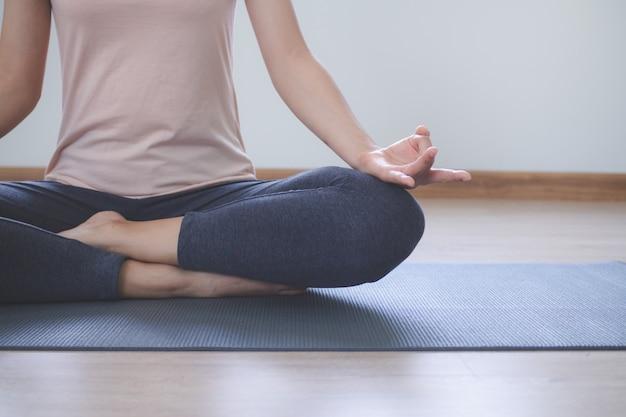 Stili di vita di yoga e meditazione. vista ravvicinata della giovane e bella donna praticare yoga namaste posa nel salotto di casa. Foto Premium