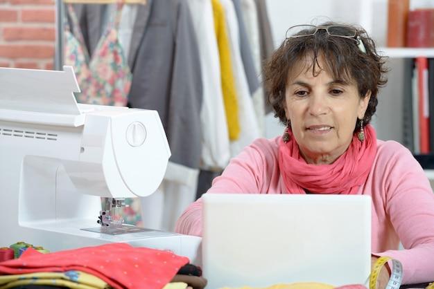 Stilista adorabile che lavora al computer portatile Foto Premium